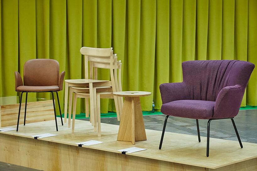 arena design 2020 - fioletowe krzesła na drewnianym podeście zzieloną zasłoną wtle