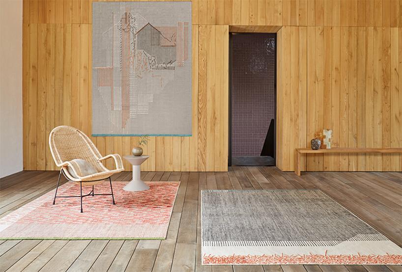 dwa dywany wpokoju wdrewnianą ścianą