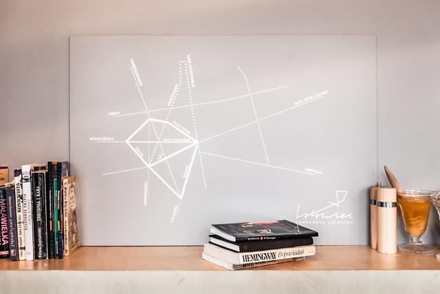 półka zksiążkami zgrafiką na ścianie