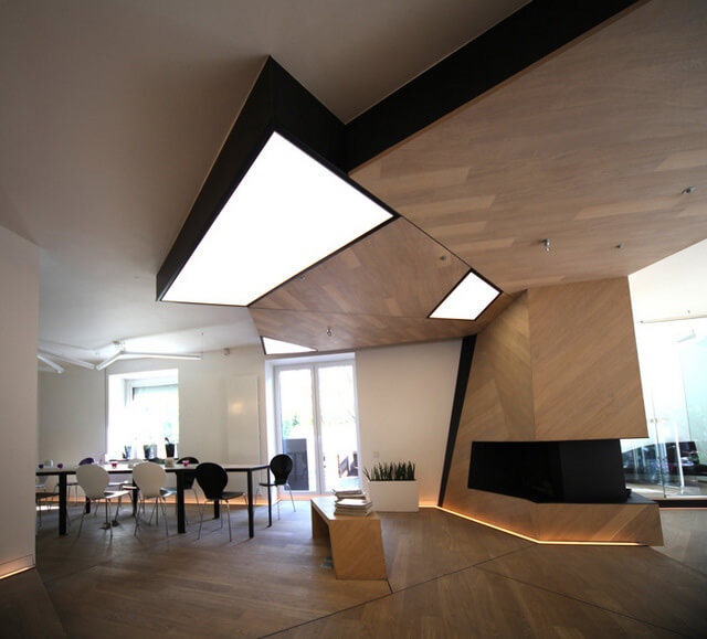 salon zdużymi lampami iczarno-białymi krzesłąmi