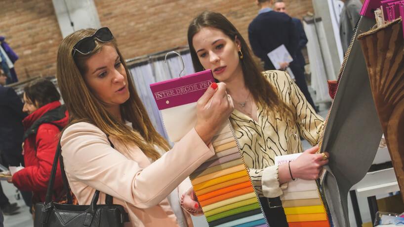 dwie kobiety oglądające próbki materiału