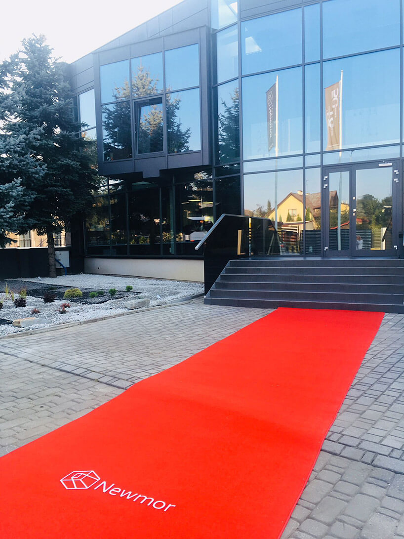 czerwony dywan znapisem Newmor rozwinięty przed wejściem do biurowca