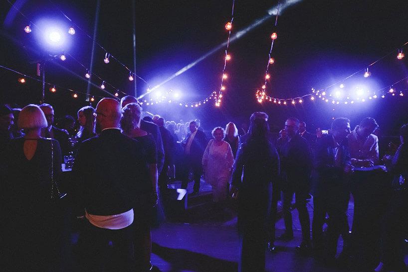 goście wdużym pomieszczeniu oświetlonym na fioletowo