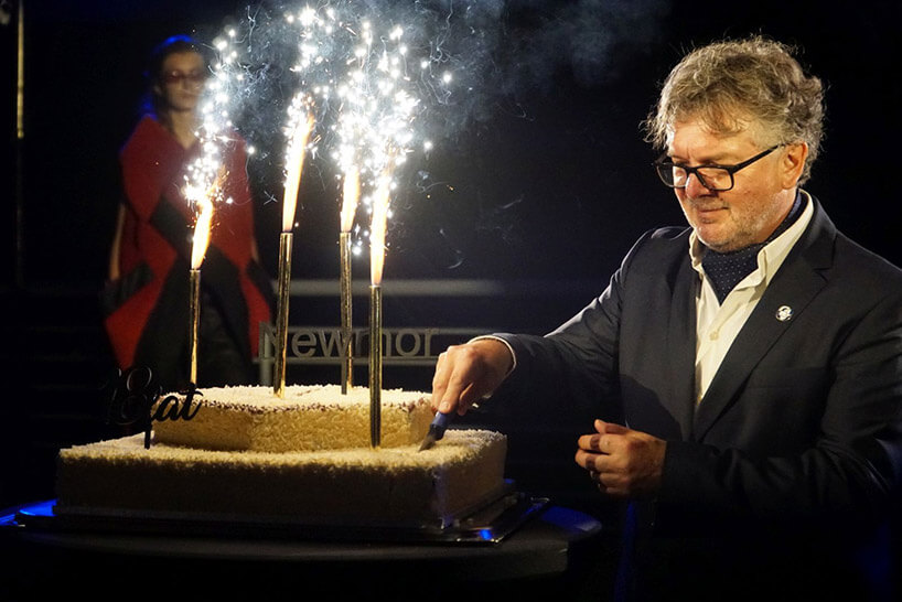 mężczyzna wokularach kroi tort zwpitymi sztucznymi ogniami