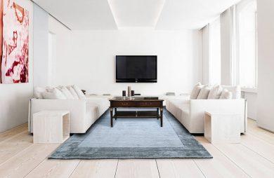 ciemno niebieski dywan w jasnym salonie
