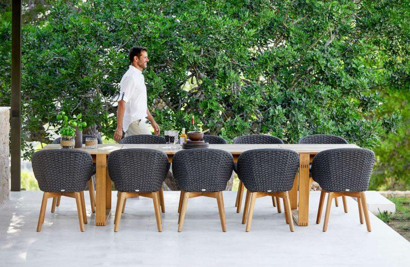zestaw krzeseł na taras wzestawie ze stołem na tle żywopłotu