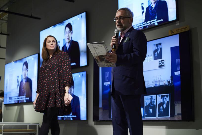 prowadzący 20-lecie BoConcept wPolsce na tle kilku ekranów