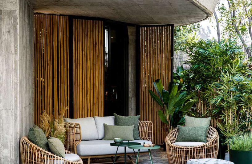 meble ogrodowe zwikliny na kamiennej podłodze przed domem wśród zieleni