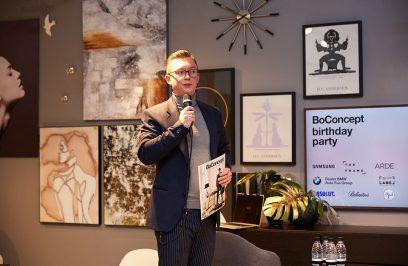 mężczyzna z mikrofonem na tle ściany pełnej obrazów