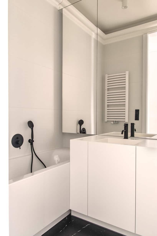 biała łazienka zprosymi matowymi białymi szafkami zczarnymi dodatkami
