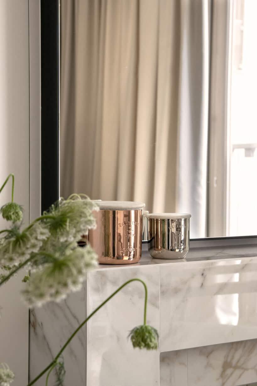 biało szary marmurek zmetalowymi pojemnikami wmiedzianym kolorze oraz zielonym kwiatkiem