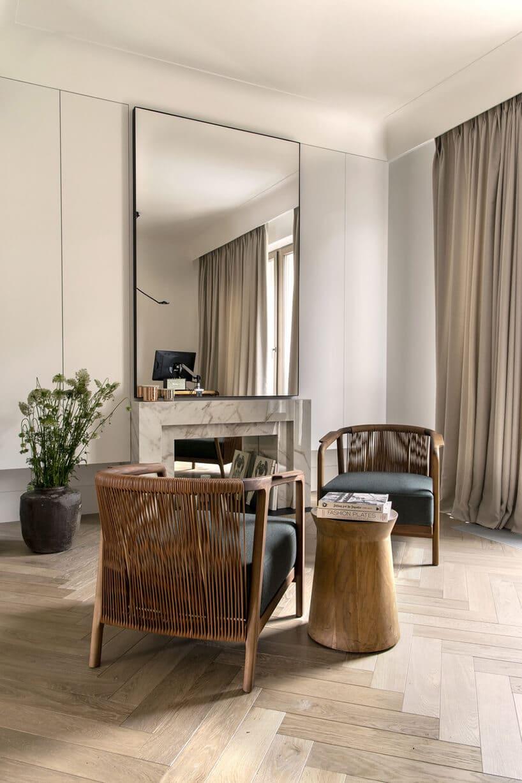salon zfotelami zratanu wkolorze brązu na drewnianej podłodze zkolebek przy dużym lustrze