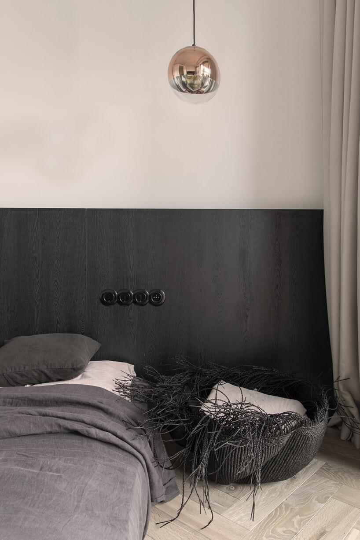 sypialnia złóżkiem małżeńskim wkolorze szarym zdużym czarnym zagłówkiem oraz koszem