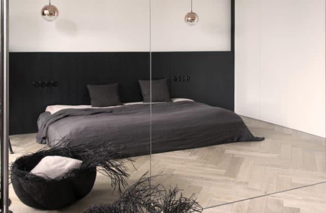 odbicie lustrzane z szarym łóżkiem z szarym plecionymi koszami
