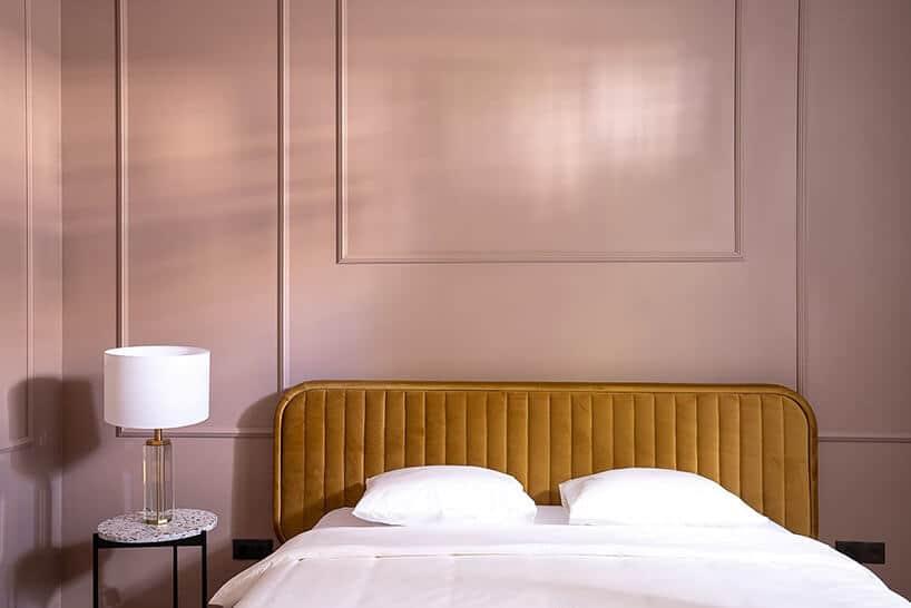 różowa ściana ze sztukateria przy brązowym łóżku