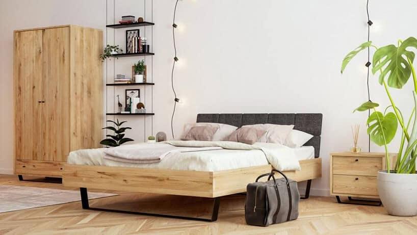 dębowe łóżko zczarną ramą oraz beżowymi poduszkami