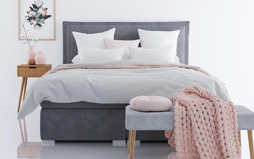 szare łóżko kontynentalne zjasno szarą pościelą oraz białymi poduszkami iróżowym kocem