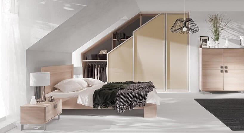 łóżko zjasne sklejki drewnianej obok szafy wkomponowanej wskos