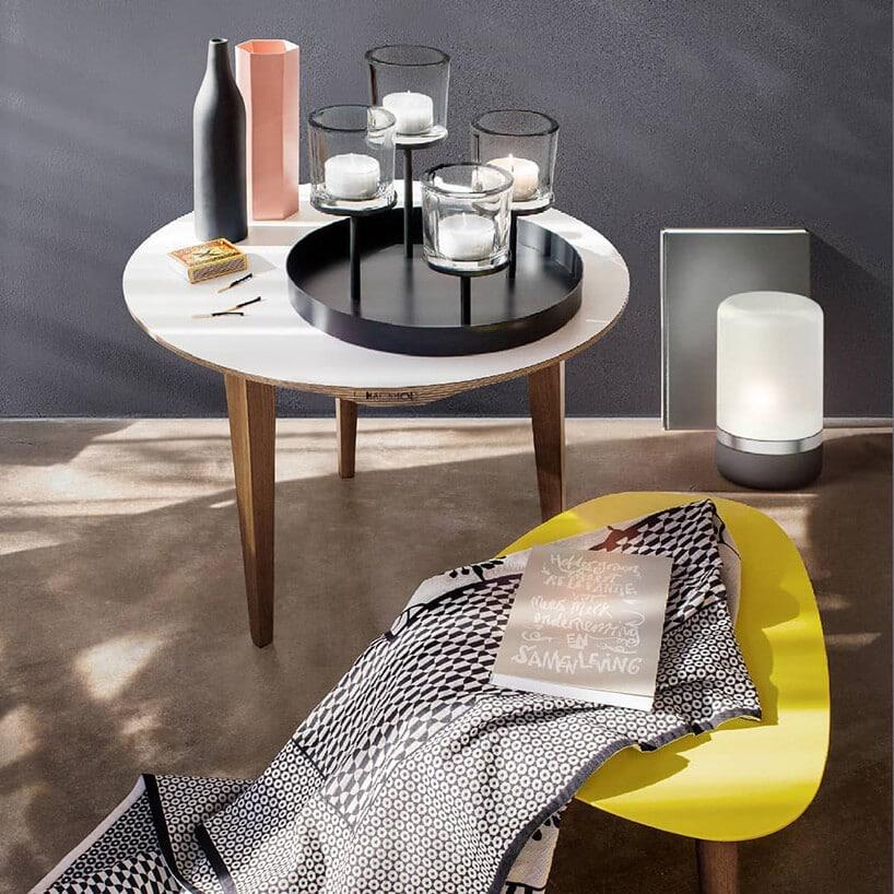 żółty stołek zmateriałem wszare kropki przy białym stoliku zczarnym świecznikiem