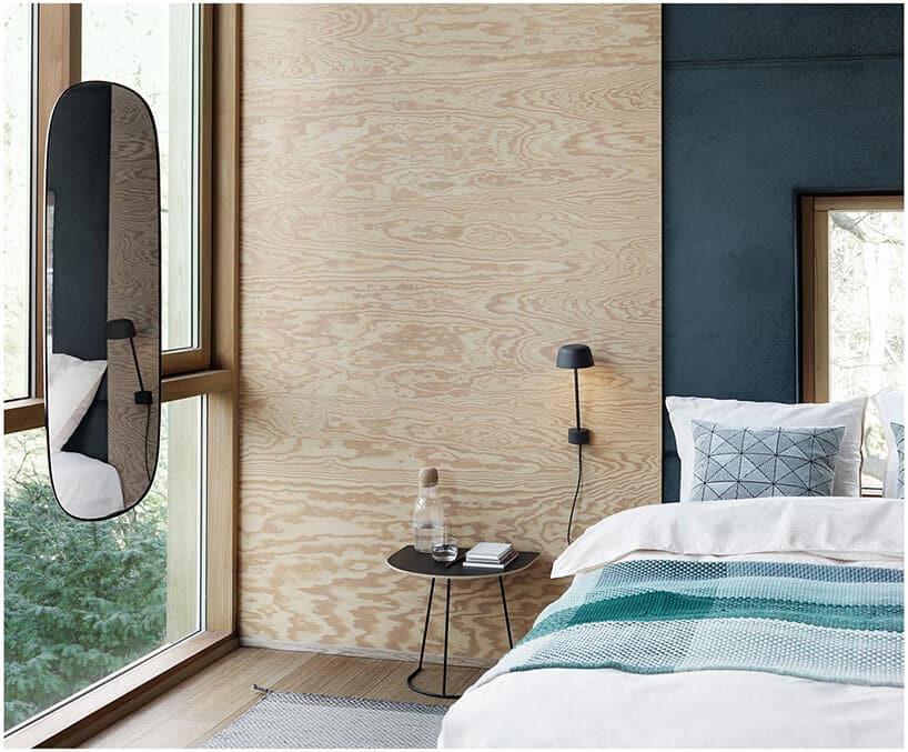 wiszące owalne lustro na otwieranym oknie przy łóżku zzielonym elementem na nażucie