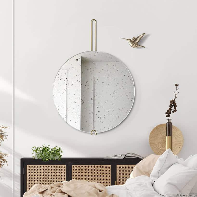 okrągłe wiszące lustro ze złotą zagiętą rurką wraz zptaszkiem na ścianie