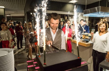 mężczyzna krojący tort ze sztucznymi ogniami