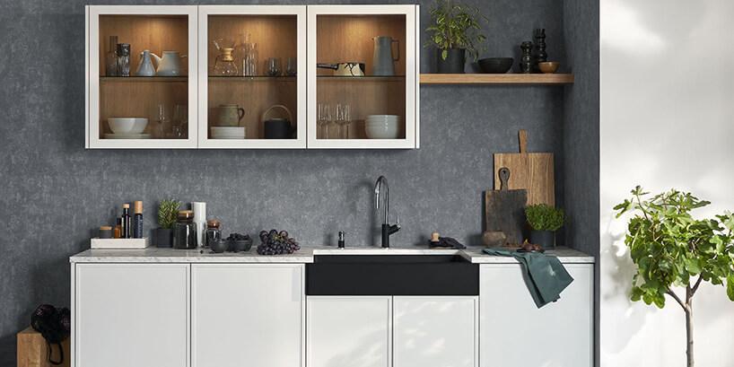 szara betonowa ściana zbiałą kuchnią oraz czarnym zlewem iprzeszklonymi szafkami