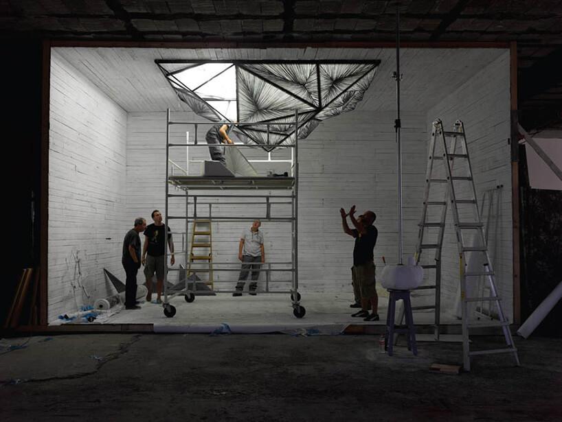 robotnicy zakładający nietypową lampę