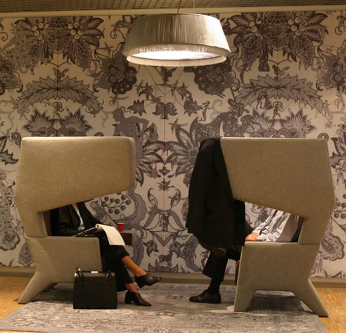 beżowe fotele zdużymi zagłówkami na tle szarej kwiecistej ściany