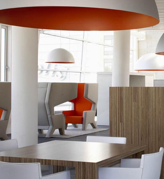 drewniany stół zbiałymi krzesłami ipomarańczową lampą