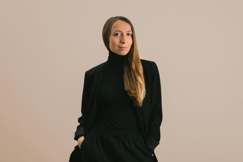 projektantka Maja Ganszyniec wczarnym stroju na beżowym tle