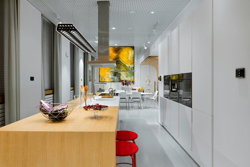 nowoczesne wnętrze Smart od ABB długa biała kuchnia zpołączoną wyspa istołem zdwoma stołkami