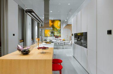 nowoczesne wnętrze Smart od ABB długa biała kuchnia z połączoną wyspa i stołem z dwoma stołkami