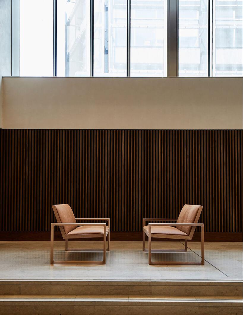 dwie drewniane sofy od Duo na kamiennej podłodze ina tle ściany zciemnych drewnianych listewek