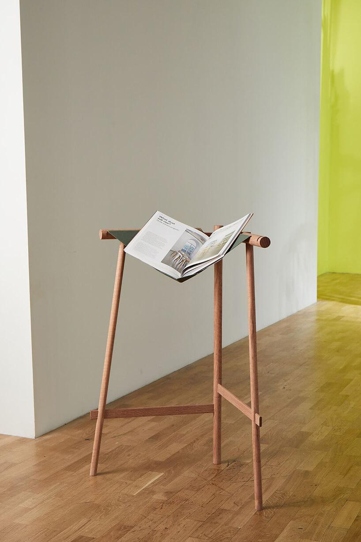 drewniany stojak na książki od Wooden Hinge na drewnianym parkiecie na tle białej ściany