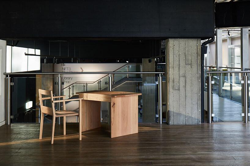 stolik ikrzesło od Writer's Collection wprzestrzeni open space zodsłoniętymi betonowymi elementami na tle metalowo szklanej barierki