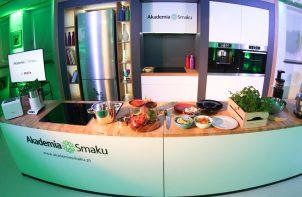 podłużna wyspa kuchenna z drewnianym blatem i produktami spożywczymi