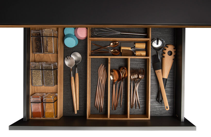 kolorowe foremki na muffinki obok narzędzi kuchennych wszufladzie