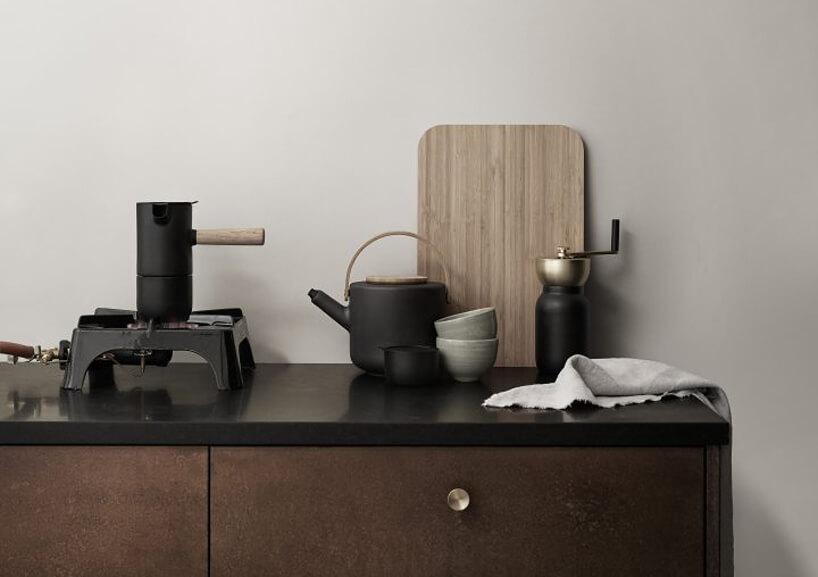 elegancka ciemna kawiarka Collar od Stelton na czarnym blacie szafki kuchennej zciemno brązowymi frontami