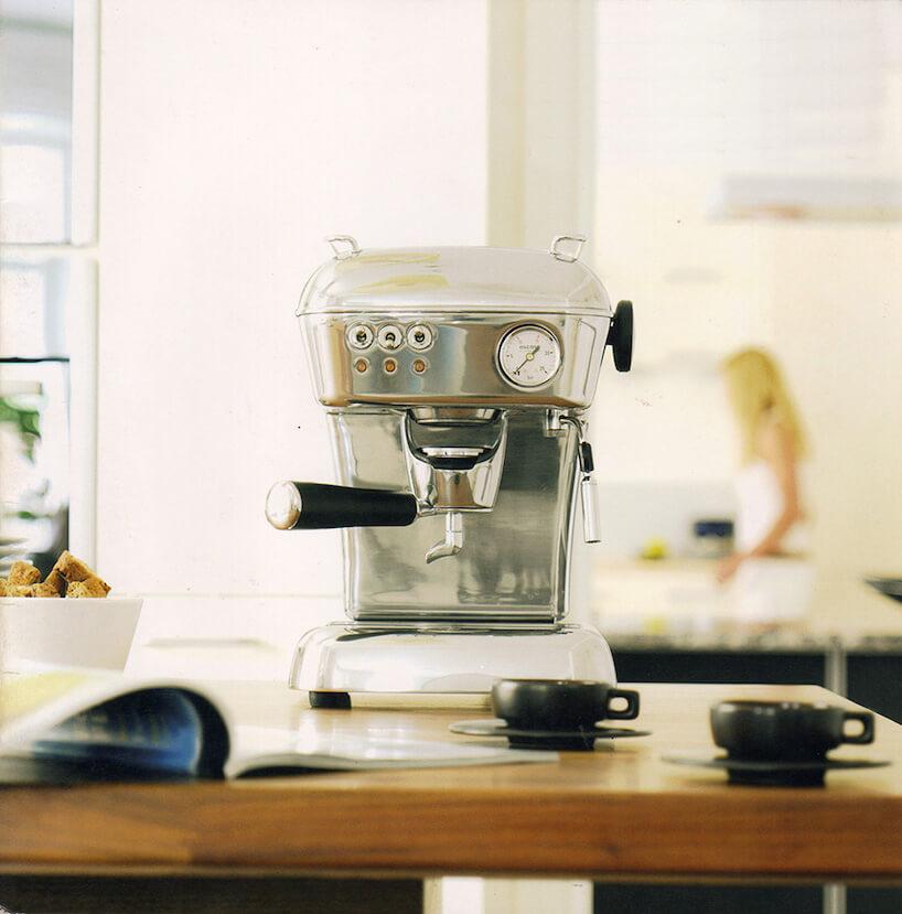 elegancki błyszczący ekspres do kawy Dream PID od Ascaso na stole zdrewnianym blatem zdwoma niskimi czarnymi filiżankami