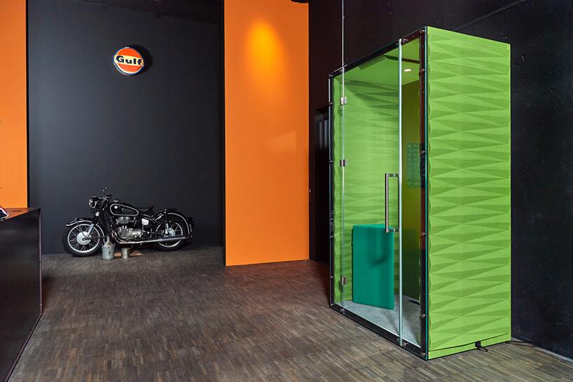 zielony box akustyczny na tle czarnej ściany obok zabytkowego motocyklaVANK_WALL BOX