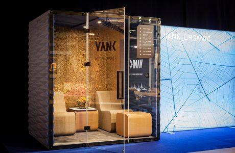brązowy box akustyczny VNAK_ORGANIC z korkowym wnętrzem dwoma krzesłami pufa i małym stolikiem