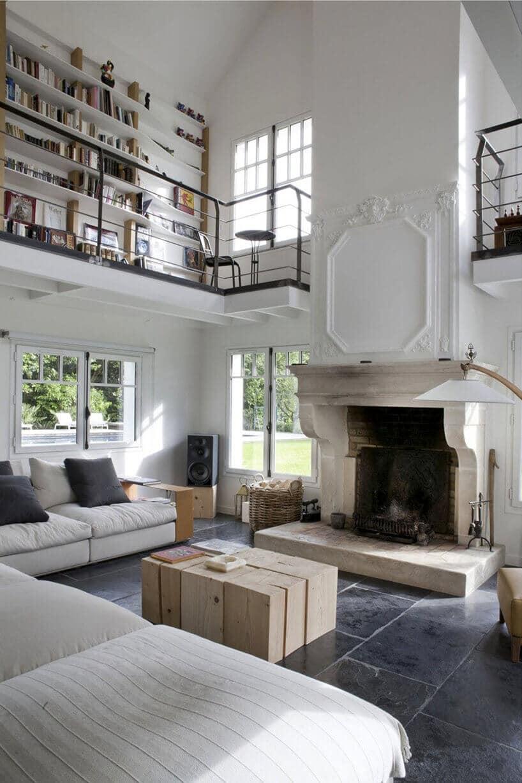 wnętrze salonu zbiałą kanapą oraz sztukaterią na kominku oraz antresolą zbiblioteczką