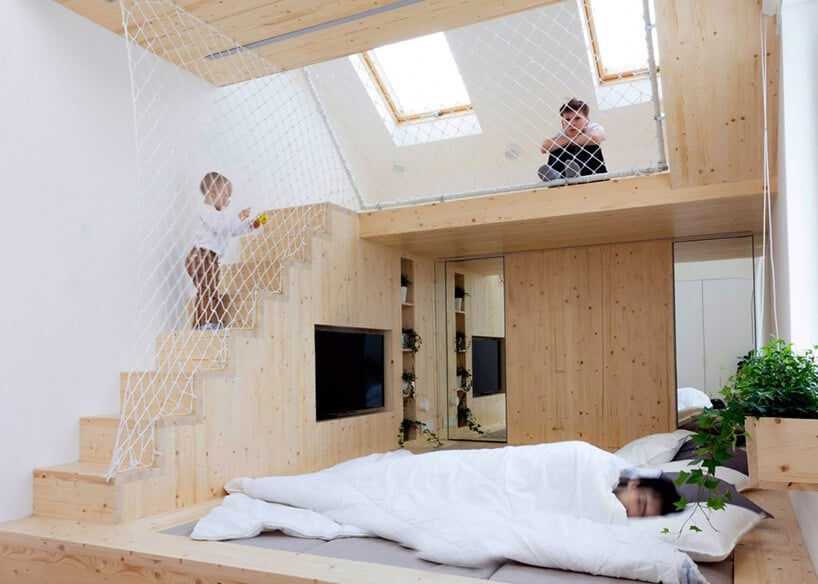 sypialnia wykonana zjasnego drewna ze chodami odgrodzonymi materiałową siadką