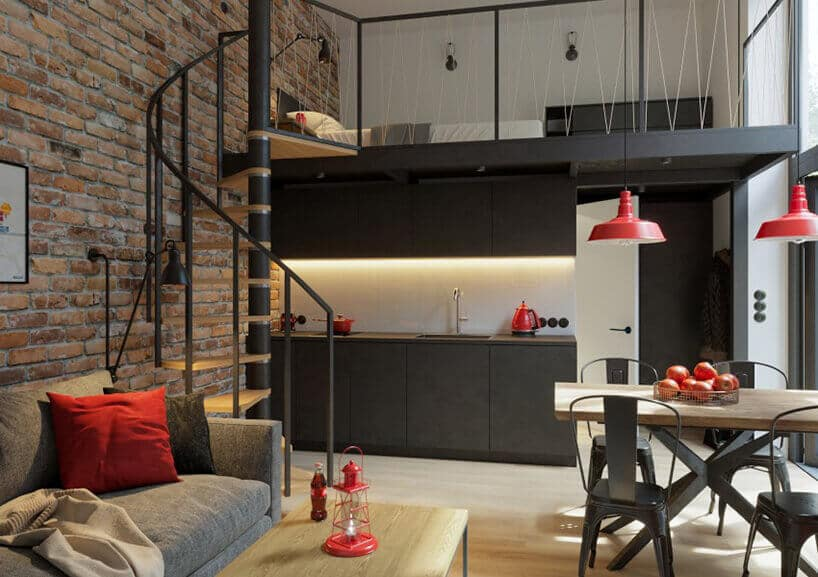 kawalerka zścianą ze starej cegły oraz kręconymi schodami na antresolę wmetalowej konstrukcji wkolorze czarnym