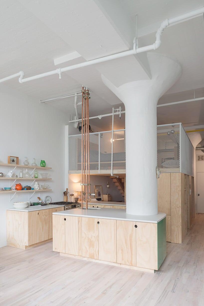 duży biały lejek podtrzymujący sufit przy jasnych meblach kuchennych