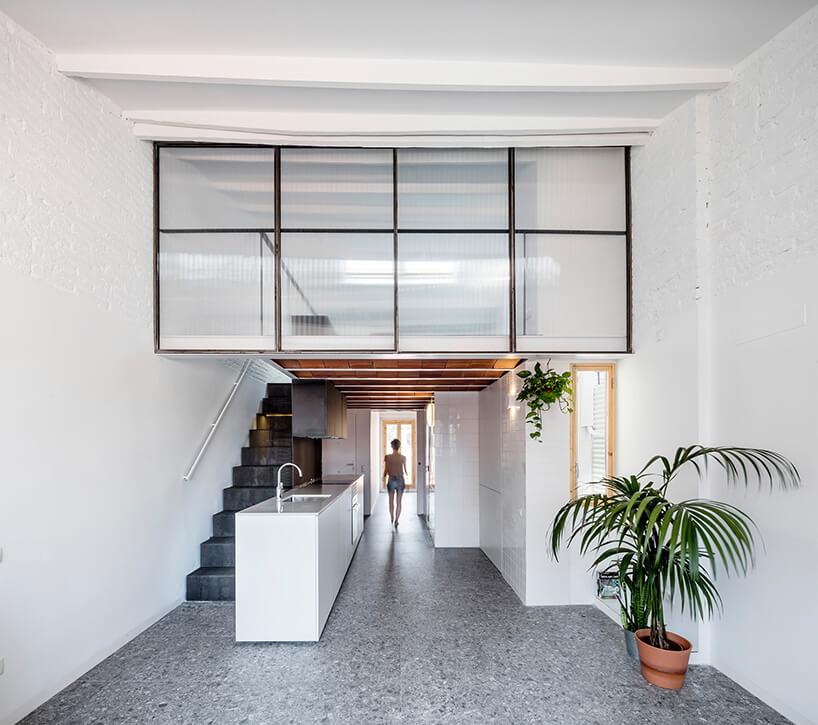 betonowa podłoga wkuchni zbiałymi połyskującymi meblami oraz antresolą