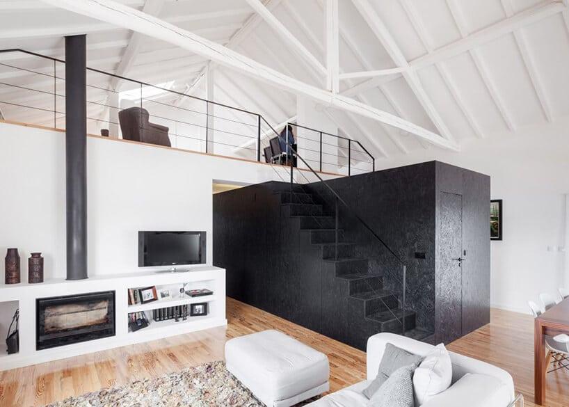 salon zczarnymi schodami oraz czarnym schowkiem pod antresolą
