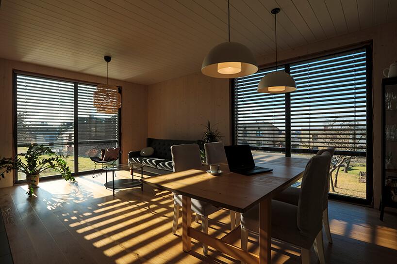 elegancki salon zdrewnianą podłogą zdużymi oknami częściowo zasłoniętymi załuzjami