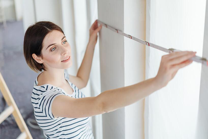 kobieta podczas remontu mierząca okna